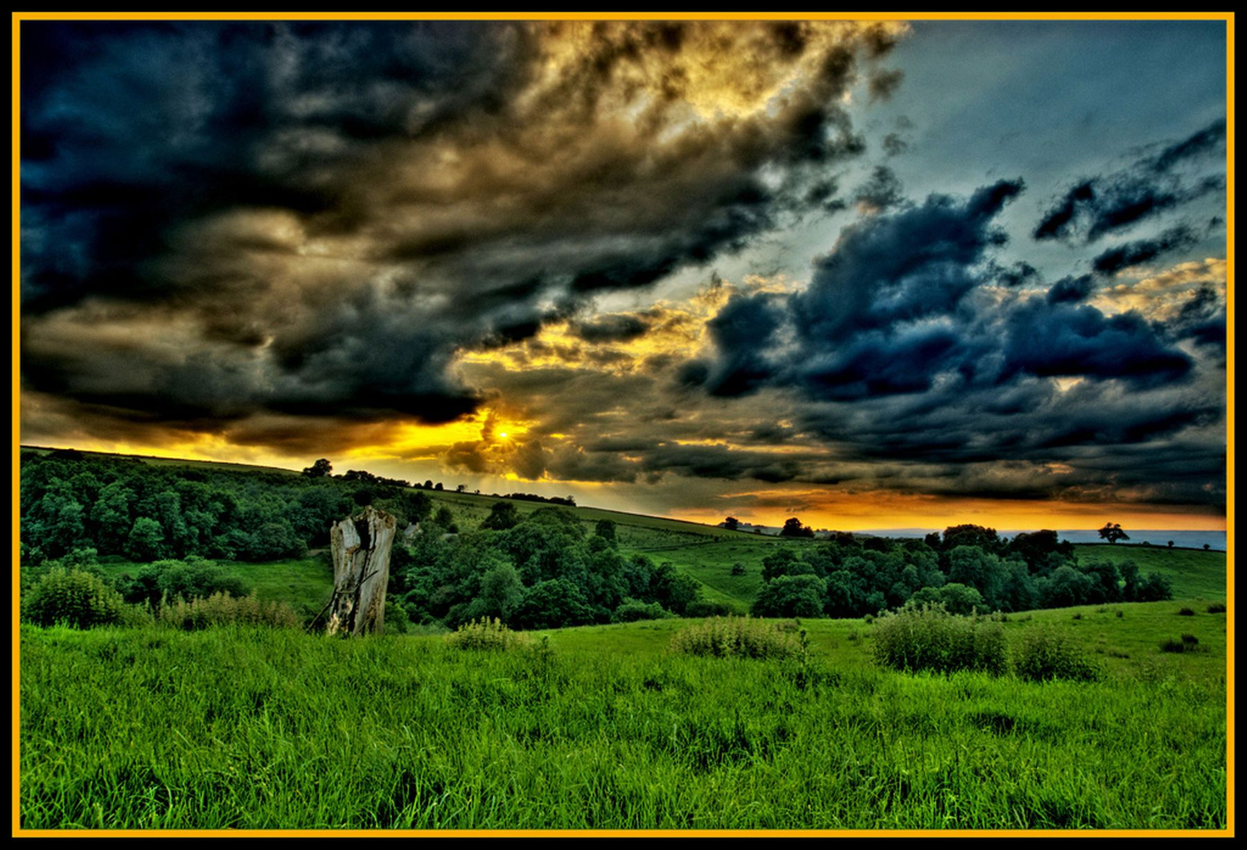 A glorious sunset with dark clouds over a field of grass